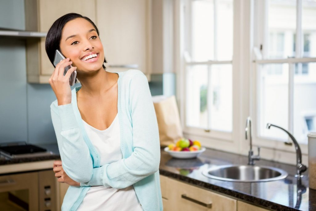 girl in the kitchen talking to her phone