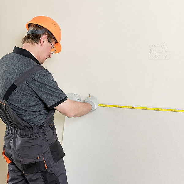 old man measuring the white wall